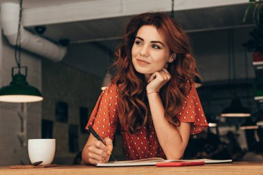 portrait of pensive blogger sitting at table with notebook in coffee shop