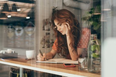 young blogger making notes in notebook at table with cup of coffee in coffee shop