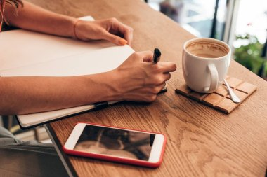 partial view of blogger making notes in notebook at table with cup of coffee in coffee shop