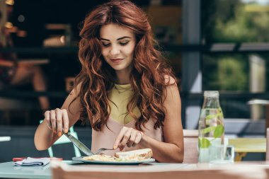 portrait of young woman having lunch alone in restaurant