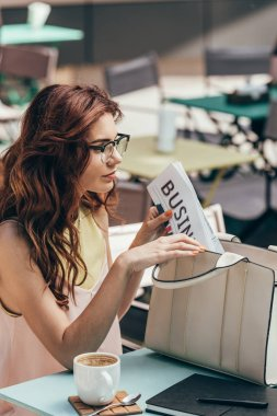 side view of young businesswoman putting business newspaper into bag in cafe