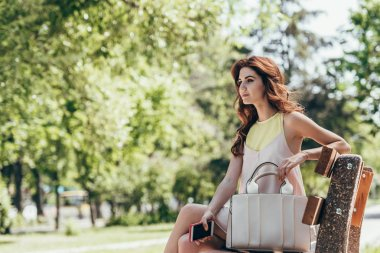 side view of young beautiful woman with smartphone in hand resting on bench in park