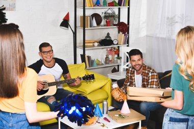 smiling young men playing guitar and looking at girls holding pizza at home party