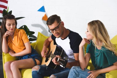 beautiful smiling girls looking at handsome young man playing acoustic guitar