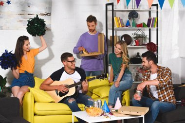 happy young friends with pizza, beer and guitar having fun together at home party