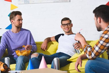 smiling young male friends drinking beer and eating snacks at home party