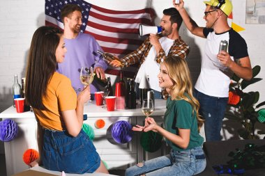 girls drinking wine and smiling each other while men partying behind