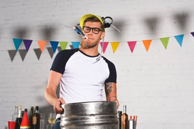 handsome young man in beer hat holding keg of beer and smiling at camera
