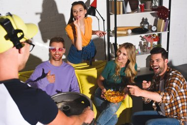 happy young people looking at male friend holding keg of beer at home party