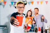 close-up view of smiling young man holding plastic cup with beer while friends partying behind