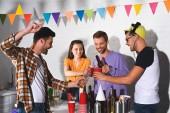Happy mladí přátelé pití alkoholu během párty společně
