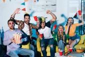 vzrušený mladí přátelé, pít pivo a jíst občerstvení doma party