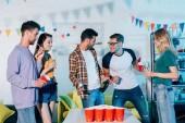 Happy mladí přátelé pití alkoholických nápojů a párty společně