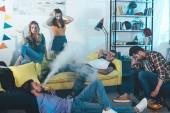 mladý muž ležící v podlaze a kouření elektronických cigaret, zatímco párty s přáteli