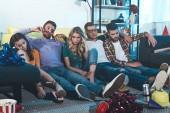opilí mladí lidé sedí na podlaze po domácí párty