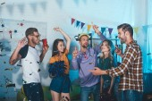 párty Happy mladí přátelé, pití alkoholu a baví doma