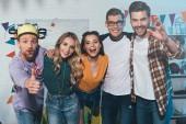 Veselý mladých mužů a žen přátel se usmívá na kameru doma večírek