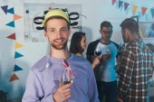 handsome young man in beer hat holding glass of wine and smiling at camera at home party