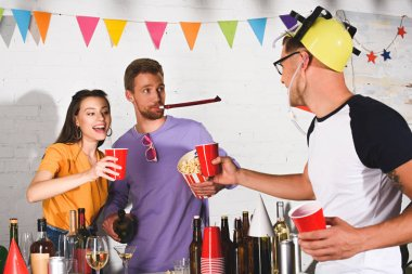 happy young people drinking alcohol and eating popcorn at home party