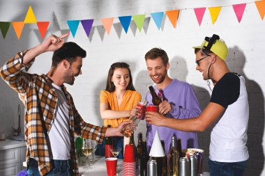 happy young friends drinking alcohol while partying together