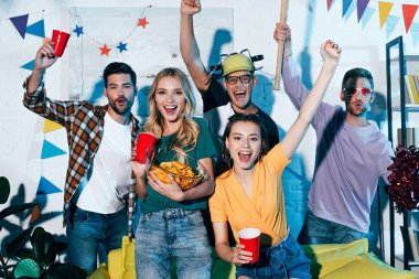 happy young men and women smiling at camera while having fun together at home party