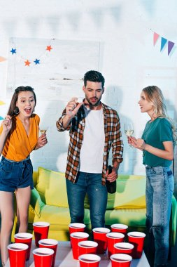 cheerful young friends having fun and playing beer pong at home party