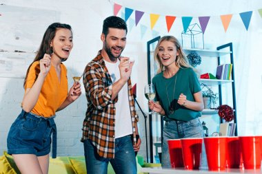 smiling girls with glasses of wine looking at young man playing beer pong at home party