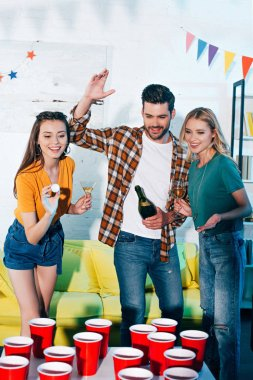 happy young male and female friends playing beer pong at home party