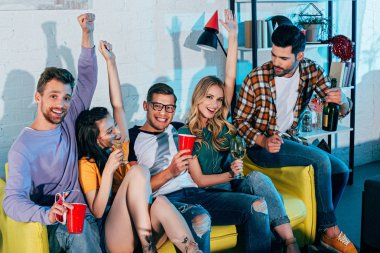 happy young friends drinking alcohol beverages and smiling at camera at home party