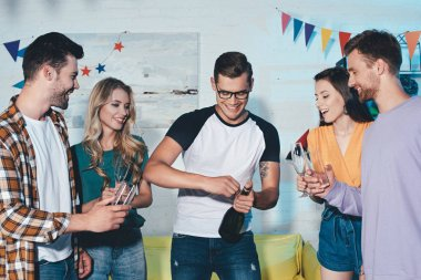 happy young male and female friends opening bottle of wine at home party