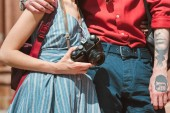 cropped view of couple with retro photo camera
