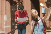 girl with camera taking selfie on smartphone while man lookoing at map