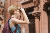 female tourist with backpack taking photo on camera in city