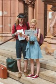 Fotografie couple of tourists with coffee reading travel newspaper while standing on stairs with retro suitcases