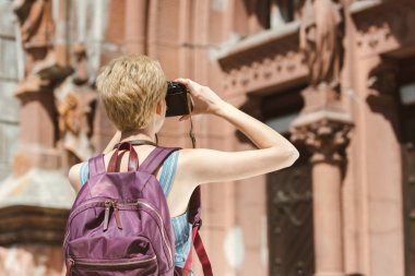 back view of tourist with backpack taking photo in city