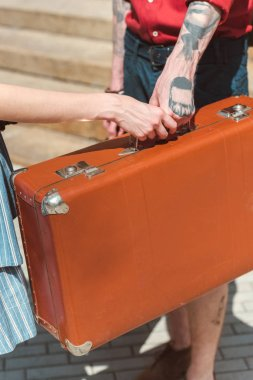partial view of couple holding retro travel bag
