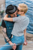 Photo boyfriend with tattoos and stylish girlfriend hugging and leaning on railing near river