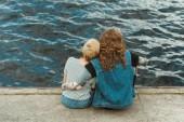 zadní pohled na pár objímání a sedí na mostě poblíž řeky
