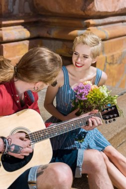 man playing acoustic guitar while girlfriend with flowers looking at him