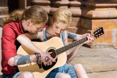 young couple playing acoustic guitar together
