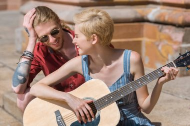 smiling stylish girlfriend playing guitar for boyfriend on street