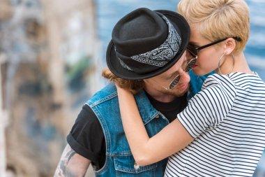 Boyfriend with tattoos and stylish girlfriend cuddling near river stock vector