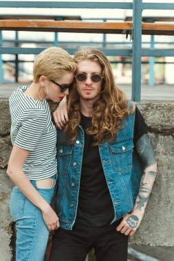 boyfriend with tattoos and stylish girlfriend posing in sunglasses near bridge