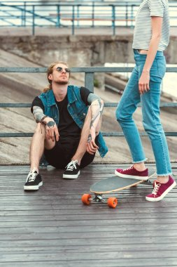 cropped image of boyfriend with tattoos sitting on bridge and girlfriend standing on skateboard