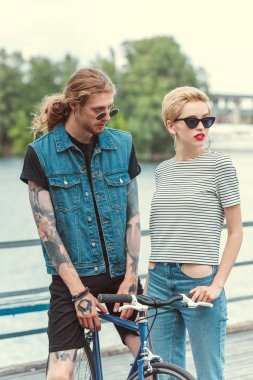 boyfriend with tattoos and stylish girlfriend standing with bicycle on bridge and looking away