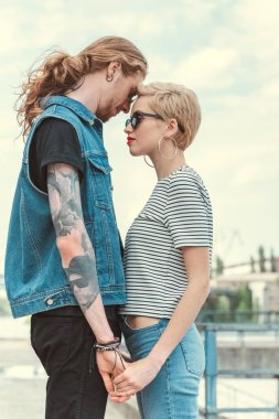 low angle view of boyfriend with tattoos and stylish girlfriend holding hands and touching with foreheads