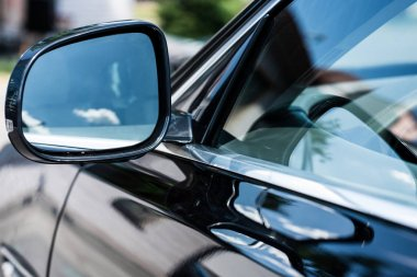 close up view of front car mirror with reflection