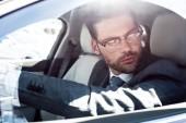 Fotografie side view of businessman in eyeglasses looking away while driving car