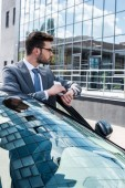 Fotografie side view of thoughtful businessman with smartphone while standing near car on street