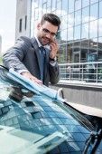 Fotografie smiling businessman talking on smartphone while cleaning front glass with rag
